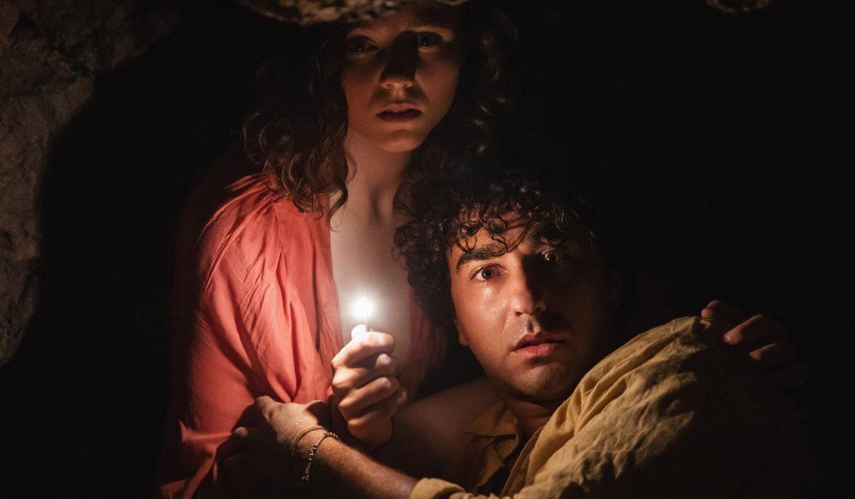 Thomasin McKenzie and Alex Wolff huddling for safety in the cave in Old.