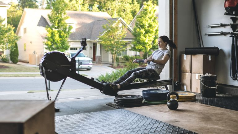 Woman in her garage using one of the best rowing machines