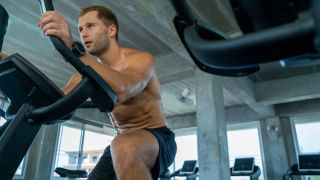 Does bike riding work your abs? Man riding exercise bike in the gym
