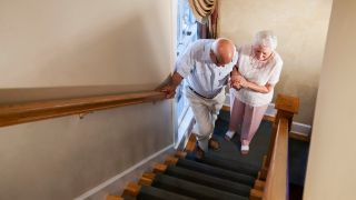Old woman struggling to help elderly man up the stairs