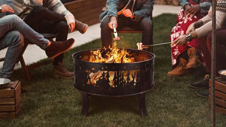 The best fire pit hero image showing humans sat around a fire pit cooking marshmallows