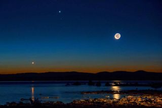 Morning twilight photo of the waning crescent moon shining over the waters of California's Mono Lake, with Jupiter nearby in the upper middle of the photo and Venus at lower left. The photo was captured on Aug. 23, 2014.