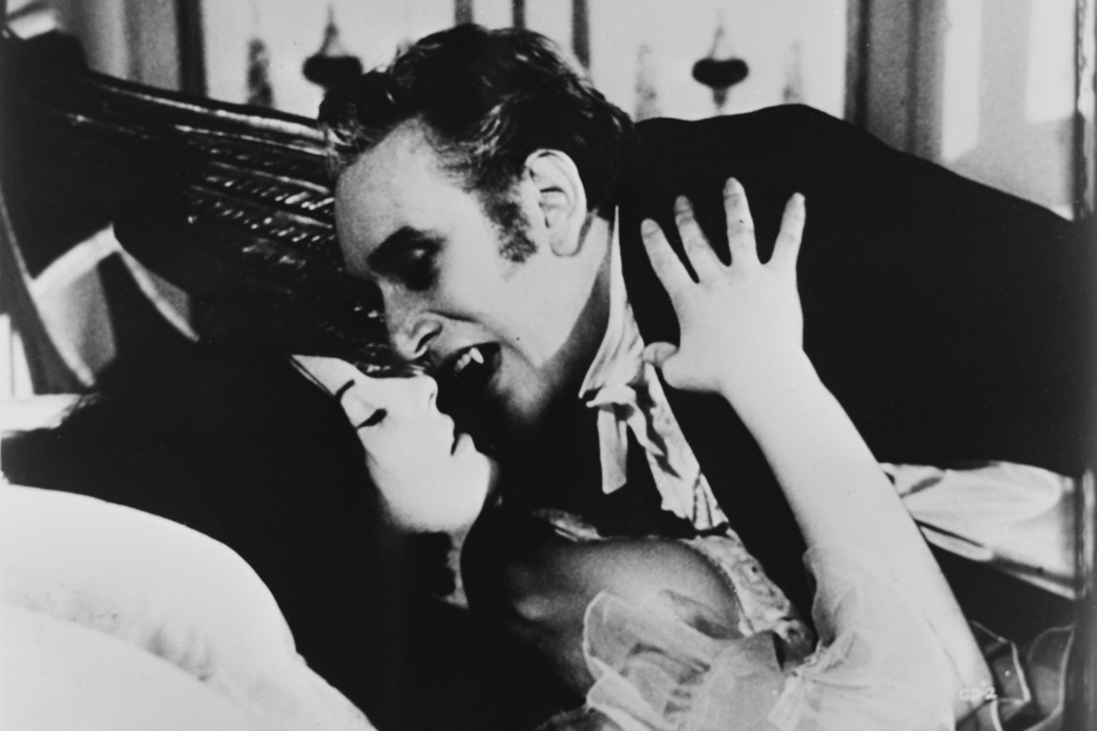 Black and white photo of a vampire about to bite a woman's neck in an old movie.