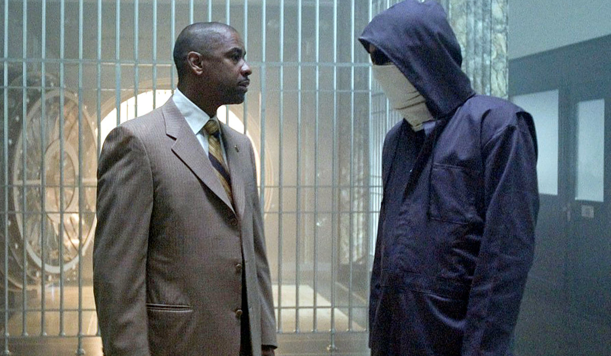 Inside Man Denzel Washington speaks with a masked person in a vault