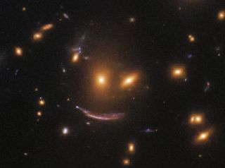 A trio of galaxies form what appears to be a wry smile in deep space in this view from the Hubble Space Telescope. This close-up image shows galaxies from the SDSS J0952+3434 cluster.