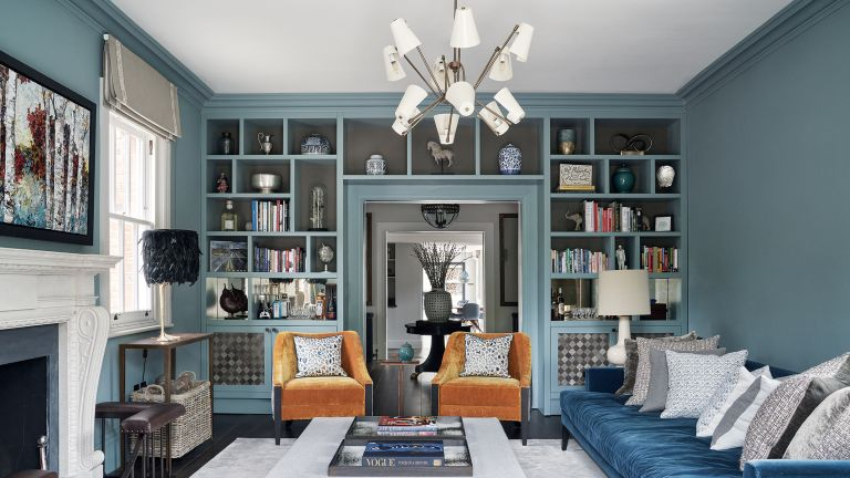 Small living room lighting ideas with blue walls, blue sofa, orange armchairs and a sputnik chandlier with coned lampshades over the bulbs
