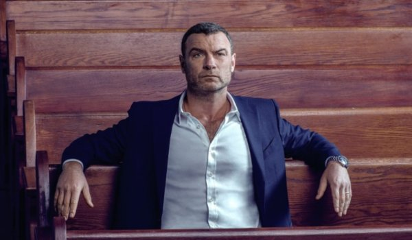 Ray Donovan sits in a pew in church