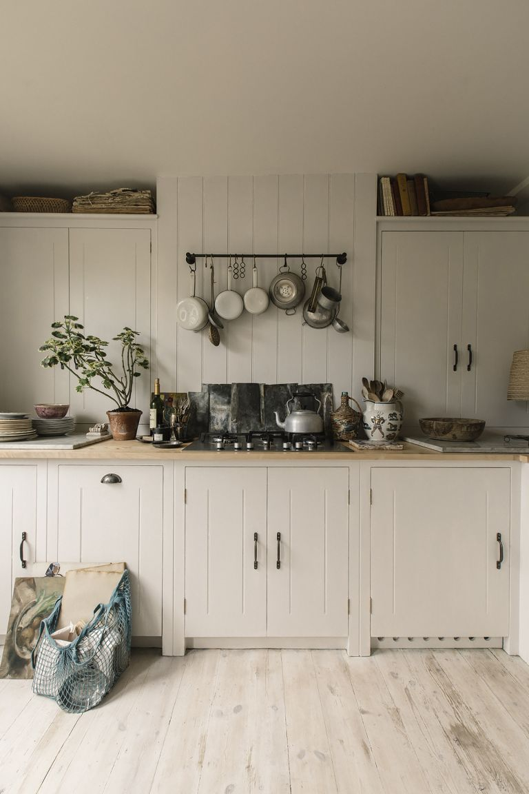 Cream kitchen ideas with standard tongue and groove cream shaker kitchen and pots hung above the stove