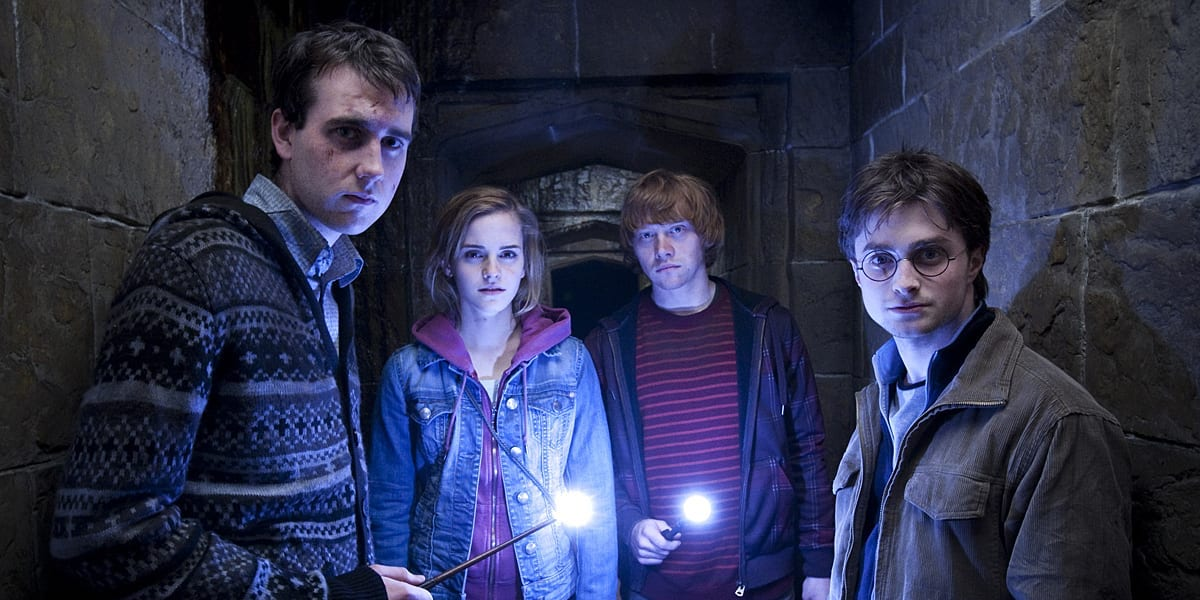 Neville Longbottom, Hermione Granger, Ron Weasley and Harry Potter hold their lit wants in the hallw
