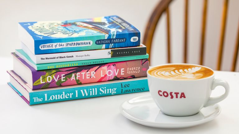 Lifestyle shot of a costa coffee cup and a stack of the Costa Book Awards 2020 category winners