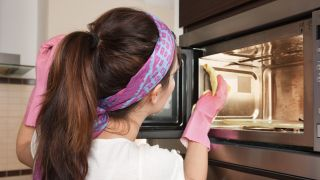 How to clean a microwave: Woman cleaning inside of microwave