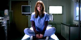 Grey's Anatomy Meredith Grey sits on a gurney in a dark hospital room.
