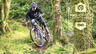A mountain biker rides through some muddy ruts