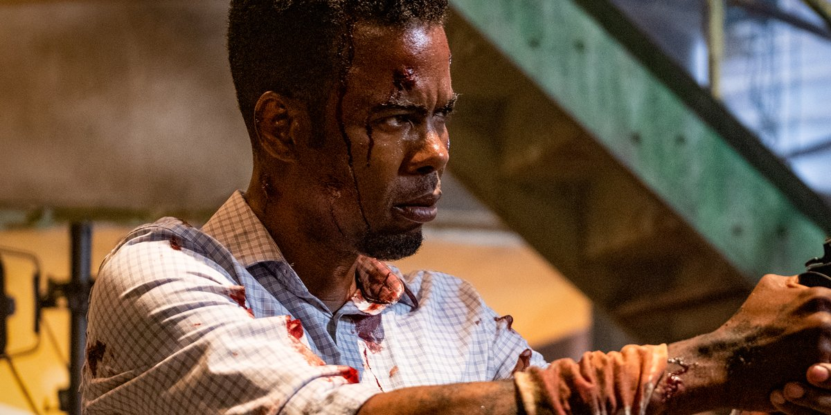 Chris Rock bloody and holding a gun in Spiral: From The Book Of Saw