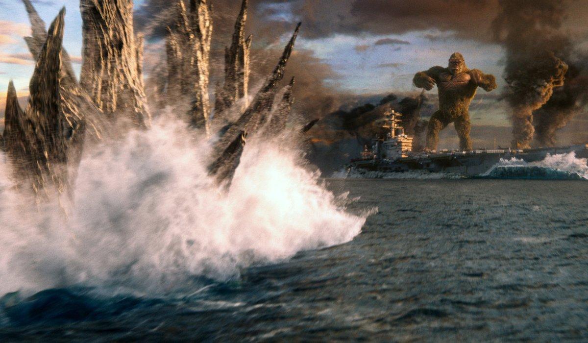 Godzilla swims towards Kong, standing on a battleship, in Godzilla vs. Kong.