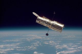 The Hubble Space Telescope drifts above the horizon of the Earth, as it has since 1990.
