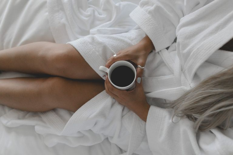 bedroom decor ideas: A young tanned woman sitting on a white bed in a white robe holding a coffee cup shot from above.