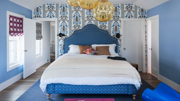 Blue bedroom with blue patterned wallpaper and statement bed