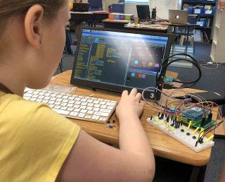 Girl works with Boolean Girl Tech's Lights, Camera, Sensors kit