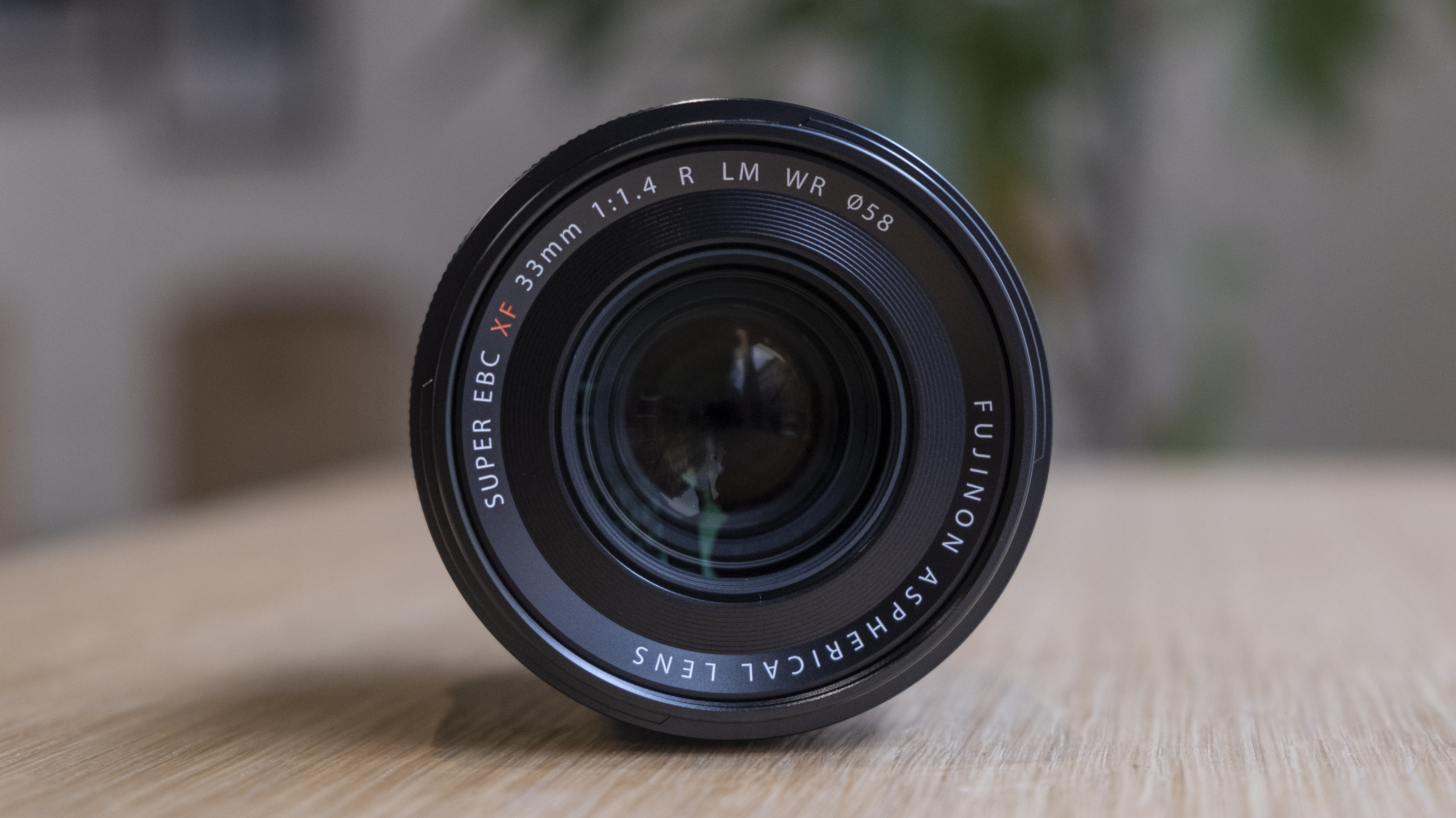 The Fujifilm XF33mm f/1.4 lens on a wooden table