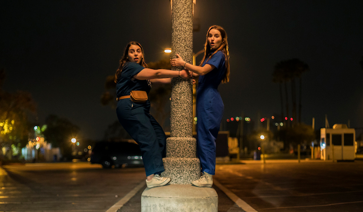 Two friends hanging on to a light post in Booksmart
