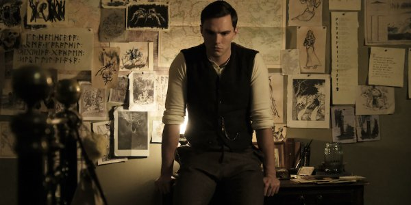 Tolkien Nicholas Hoult sits on the edge of his desk, thinking