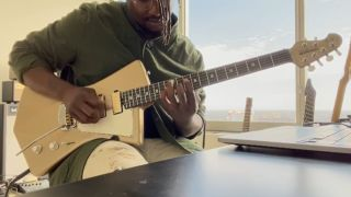 Tosin Abasi playing a St. Vincent signature Goldie Ernie Ball Music Man guitar