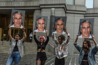Members of a protest group hold up signs of accused sex trafficker Jeffrey Epstein, in front of the federal courthouse in New York City on July 8, 2019.
