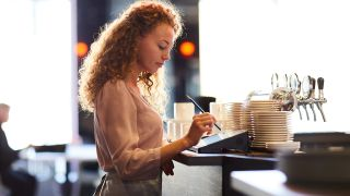 woman using a POS system in a restaurant