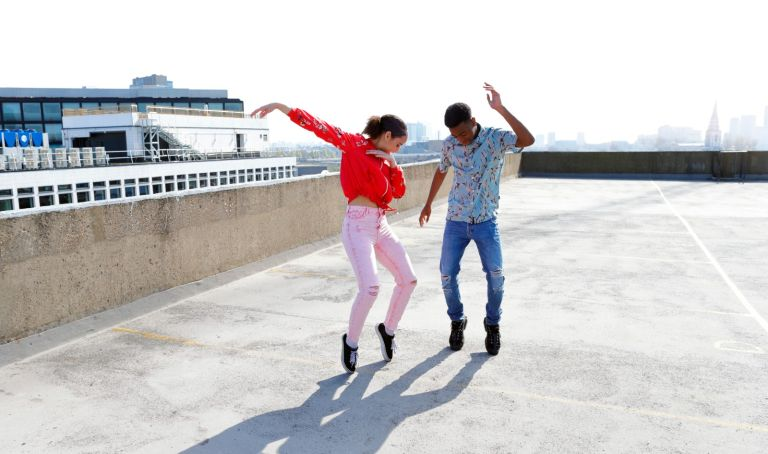 Teenagers dancing on a London rooftop overlooking the city. - stock photo