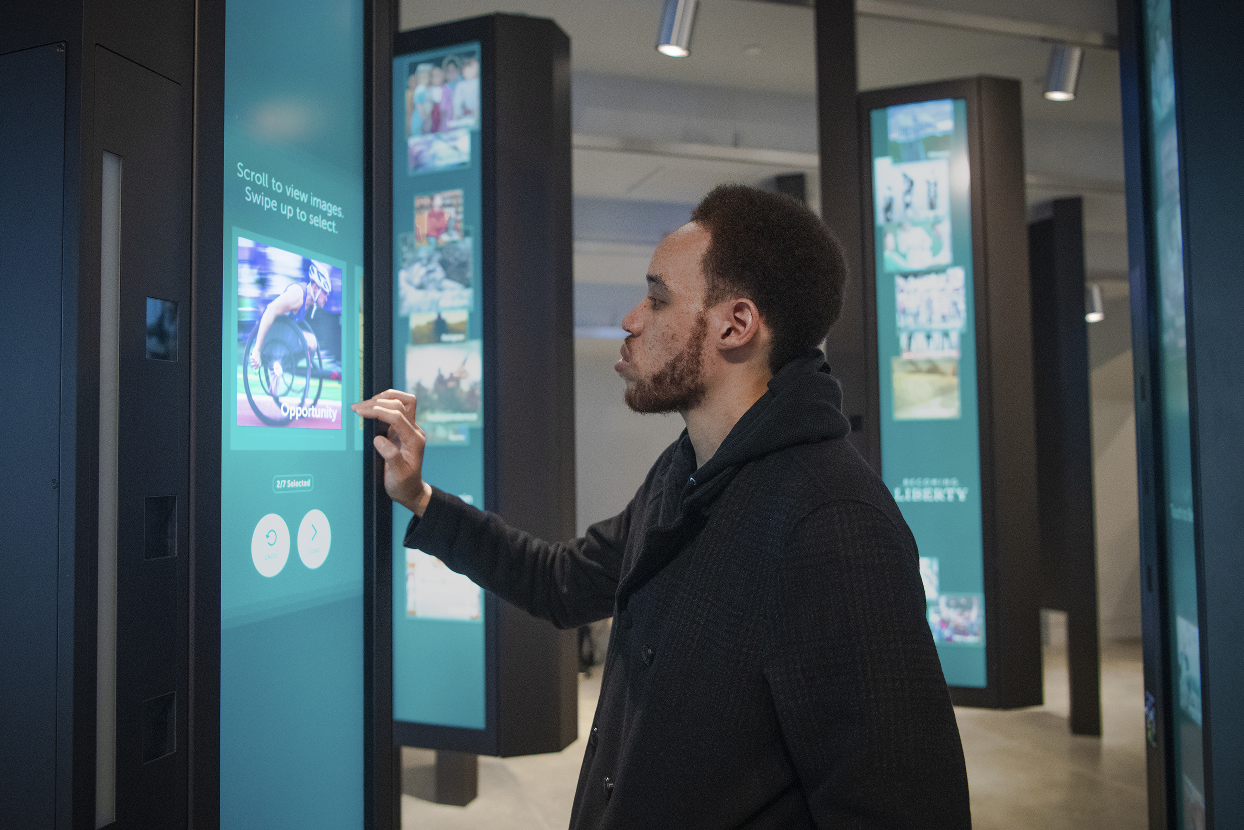 """At New York's Statue of Liberty Museum, a visitor participates in Becoming Liberty at one of 20 kiosks by choosing seven images that represent """"liberty"""" to them."""
