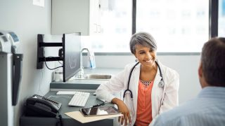 Patient speaks to smiling female doctor in a clinic.