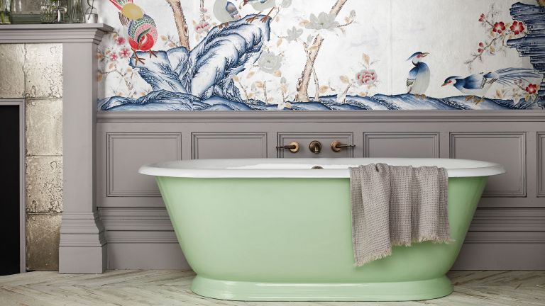green freestanding bath in bathroom with patterned wallpaper