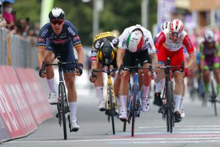 Team AlpecinFenix rider Belgiums Tim Merlier L crosses the finish line to win the second stage of the Giro dItalia 2021 cycling race 179 km between Stupinigi and Novara Piedmont on May 9 2021 Photo by Luca Bettini AFP Photo by LUCA BETTINIAFP via Getty Images