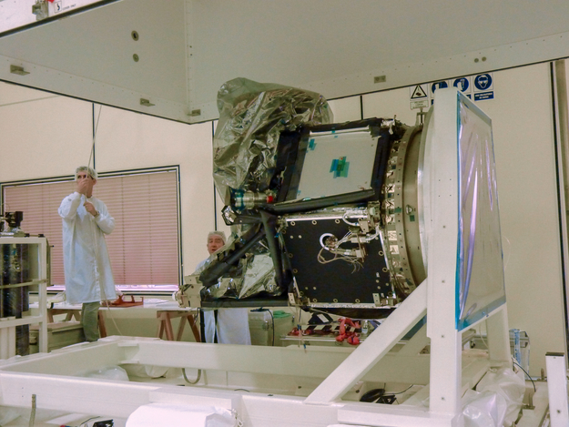 A test engineer lowers the upper part of a test container over CHEOPS in preparation for a propulsion-module leak test.