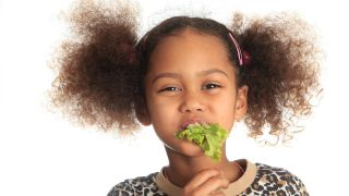 A smiling girl has a mouthful of lettuce.