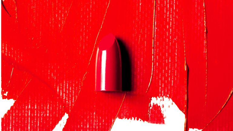 Red lipstick swatch and lipstick bullet on white background