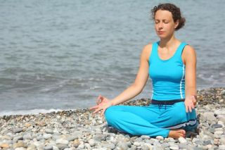 woman meditating on beach