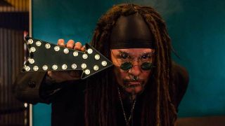 Al Jourgensen from Ministry holding an arrow to his head