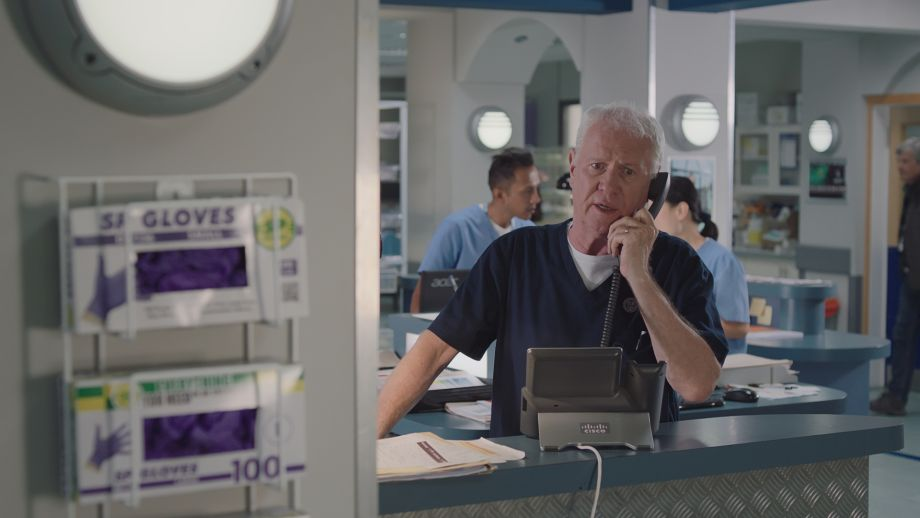 Worried Charlie in Casualty on the phone at work