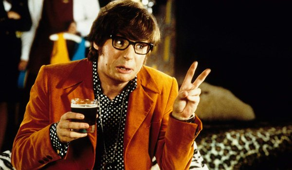 Austin Powers: International Man of Mystery giving the peace sign while having a drink