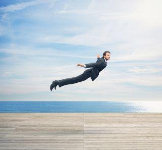 A man in a business suit flies over a boardwalk.