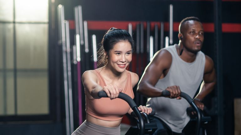 Man and woman on exercise bikes undergoing HILIT training