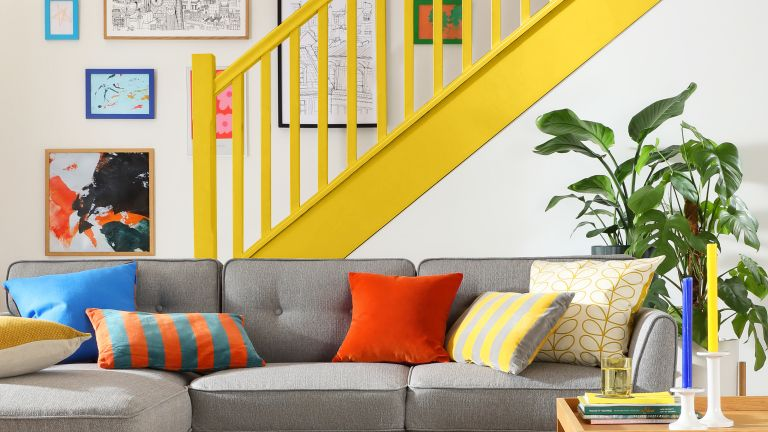Grey L Shaped Sofa with colorful cushions with yellow staircase paint idea in background