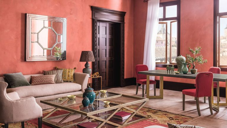 A pink living room with terracotta walls and dark woodwork