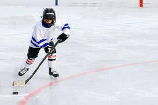 A boy plays hockey on an ice rink