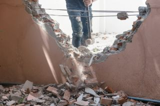 a person knocking down a wall in their home