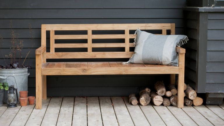 A wooden garden bench against a dark painted outdoor wall