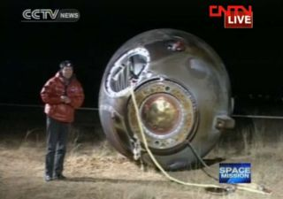 A CNTV reporter stands next to China's Shenzhou 8 space capsule on Nov. 17, 2011 after the unmanned spacecraft landed in inner Mongolia after a nearly two-week mission that successfully performed China's first space dockings in orbit.