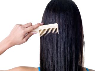 A woman combs her long hair